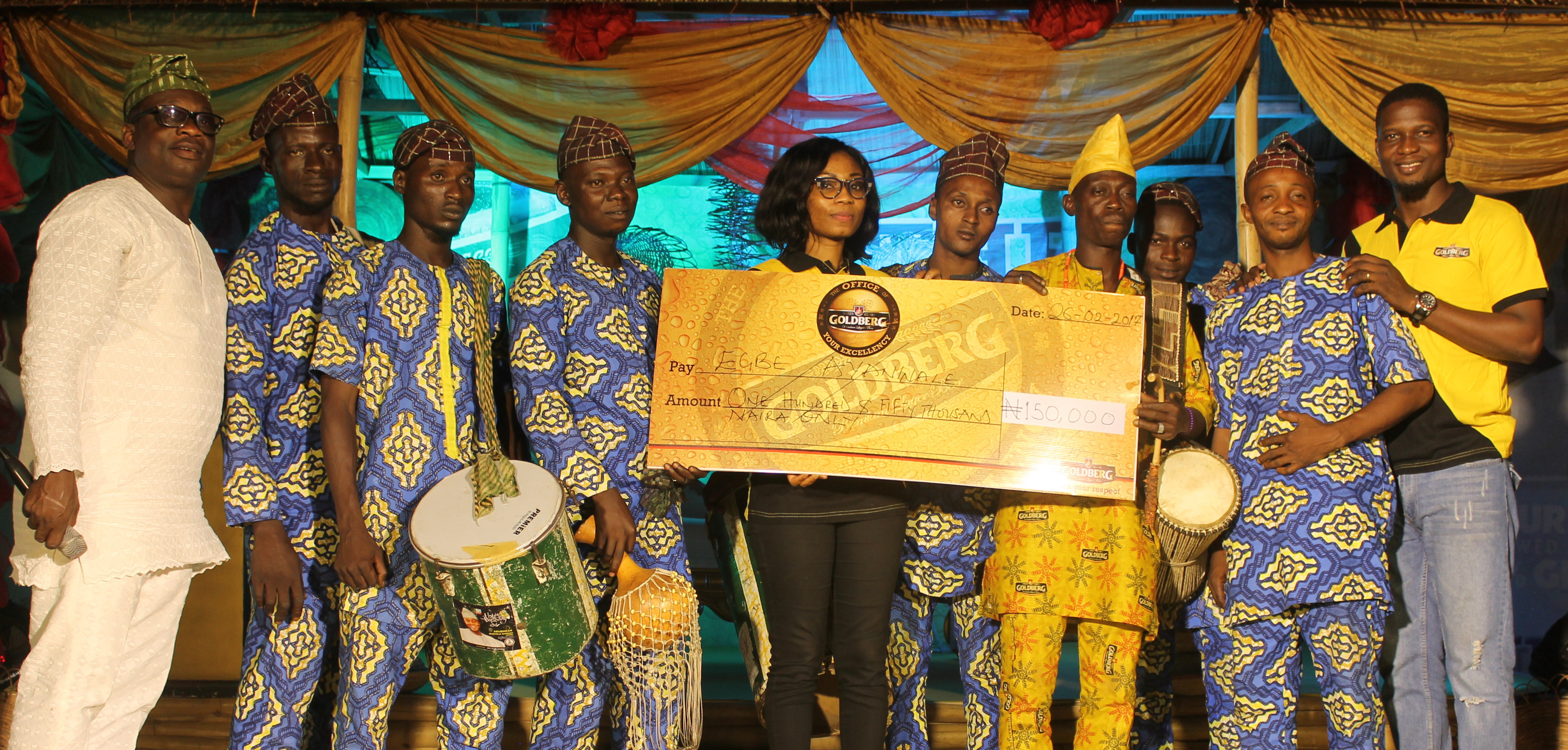 Ayotola Owolabi, Assistant Trade Marketing Manager, Nigerian Breweries Plc, presenting a cheque of One Hundred and Fifty Thousand Naira to Egbe Ayanwale Band, winner of the second prize at the Goldberg Excellency Tour in Ilorin on Sunday. With them are Muyiwa Oshinaike, chief judge of the Traditional Drummers Contest (1st from left) and Josiah Akinola, Assistant Brand Manager, Regional Mainstream Brands, Nigerian Breweries Plc (1st from right).